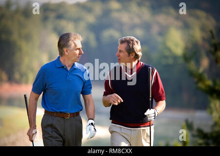 Two mature men enjoying a game together on a golf course. - Stock Photo