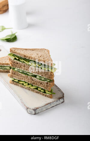 Healthy vegan sandwiches  with green vegetables and greens. Avocado, spinach and cucumber toasts on cutting boardover white background. Plant based fo - Stock Photo