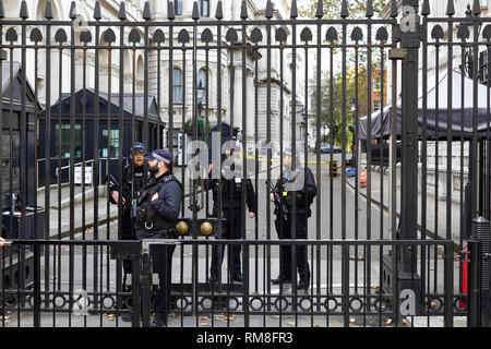 Armed police behind the gates of 10 Downing Street London - Stock Photo
