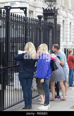 Tourists looking through the iron gates at Downing Street. - Stock Photo
