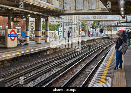 LONDON UNDERGROUND OR TUBE TRAIN ARRIVING AT ACTON TOWN STATION ON PICCADILLY LINE - Stock Photo
