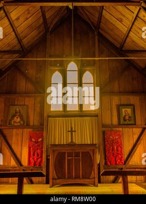Maori wood carvings and Christian images, mellow golden light on bare wood lined walls, Pepara Church, Koriniti Marae, Whanganui River,  New Zealand - Stock Photo