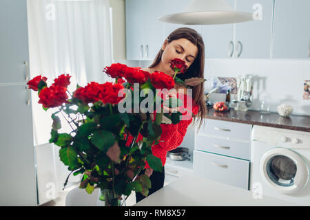 Woman puts pink roses in vase smelling flower. Young housewife taking care of coziness on kitchen. Modern kitchen design. Valentine's day - Stock Photo