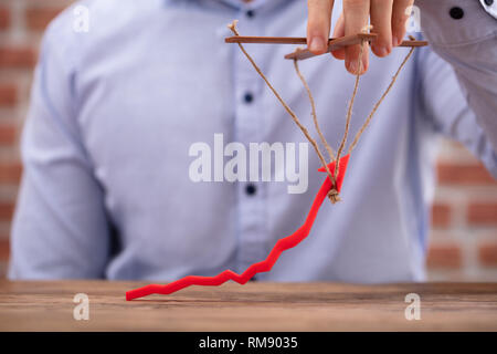 Mid-section Of Person's Hand Manipulating Blue Arrow With Rope - Stock Photo