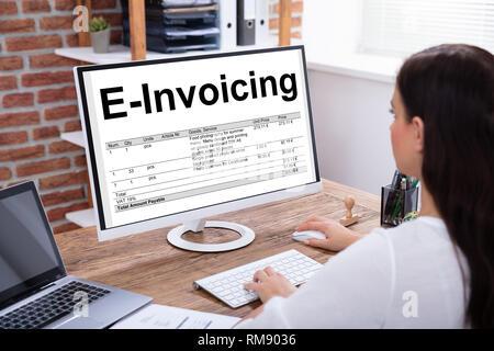 Close-up Of A Businesswoman Preparing E-invoicing Bill On Computer Over Wooden Desk - Stock Photo