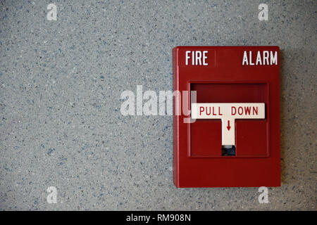 Wall mounted metal red fire alarm box with white pull down handle. - Stock Photo