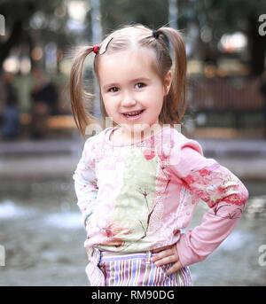 portrait of happy little girl near fountain in city Park