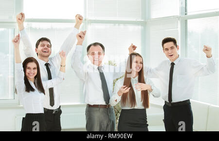 group of happy young people in formal wear celebrating, gesturing, keeping arms raised - Stock Photo