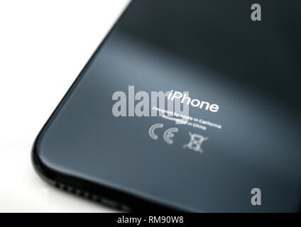 PARIS, FRANCE - NOV 5, 2017: Macro detail of rear view of latest iPhone XS Telephone Smartphone with Designed by apple in California Made in China sign on the glass back tilt-shift lens focus - Stock Photo