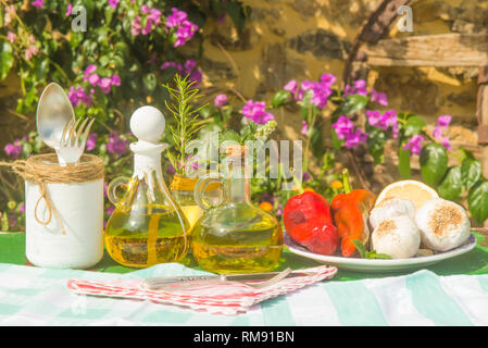 Extra virgin olive oil in vintage two glass bottles, garlic, peppers, rosemary and mint on old table in summer garden - Stock Photo