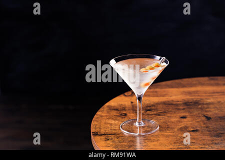 Refreshing Vodka Martini Cocktail with Olives on a Table - Stock Photo