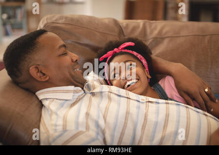Happy African American father and daughter relaxing on the sofa and looking each other - Stock Photo