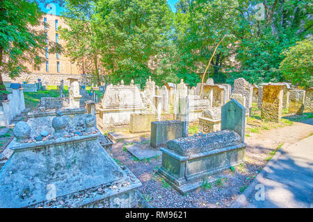 The historical Old Jewish Cemetery in Kazimierz district surrounded with lush garden and shady trees, Krakow, Poland - Stock Photo