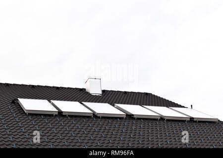 Hot water solar panels on house roof - Stock Photo