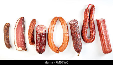 Line of assorted spicy seasoned sausages and a portion of cured ham, bacon or kassler isolated on a panorama banner format white background - Stock Photo