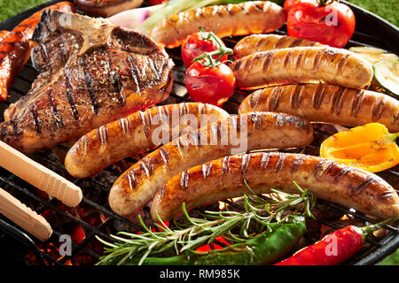 Outdoor summer barbecue with meat grilling on a fire in a close view of pork sausages, t-bone steak, fresh bell peppers, chili, tomato and zucchini ga - Stock Photo