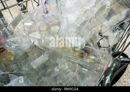 Trolly full of plastic waste in the aisles of a supermarket - Stock Photo