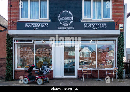Shop front Exterior of village cafe with a customers mobility scooter parked outside - Stock Photo