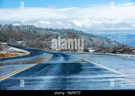 Winter landscape with wet melting road and hills with snow-covered trees, meadows and road shoulders and mountains hidden in the hanging clouds in the - Stock Photo