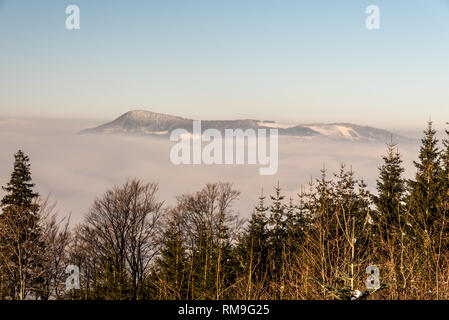 Ondrejnik mountain ridge with highest Skalka hill in Podbeskydska vrchovina mountains above mist level from hiking trail to Lysa hora hill in Moravsko - Stock Photo