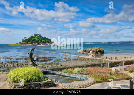 21 June 2018: Marazion, Cornwall, UK - St Michael's Mount from Marazion, with a dolphin fountain in the forground. People can be seen making their way - Stock Photo