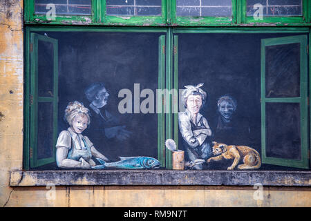 Worn out faded mystical mural with a life scene of a fishing town with people and animals painted on a walled window opening in the wall of an old bui - Stock Photo