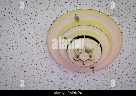 Old and dirty smoke detector with cobwebs on ceiling wall. Fire alarm system in house doesn't work. Emergency equipment in apartment need to clean and - Stock Photo