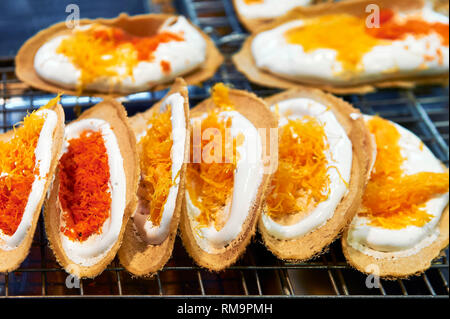 Sweet colorful Khanom Buang crepe pastries sold at a stall inside MBK Shopping Center in Bangkok, Thailand - Stock Photo