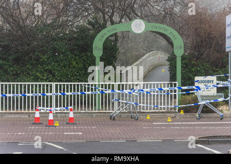 Trowbridge, Wiltshire, UK. 14th February 2019. Overnight there was a double stabbing near the Tesco Extra store. One victim rumoured to be critical. View of the Bridge into the Country park with crime scene markers leading over the bridge Credit: Starsphinx/Alamy Live News - Stock Photo