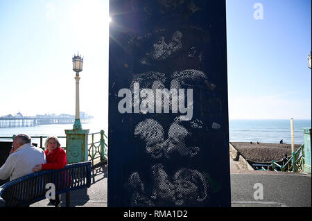 Brighton UK 14th February 2019 - Sun kissed Brighton seafront by the famous Kiss Wall sculpture by artist Bruce Williams as mild warm weather is forecast to spread across Britain with temperatures expected to reach the mid teens centigrade in some areas Credit: Simon Dack/Alamy Live News - Stock Photo
