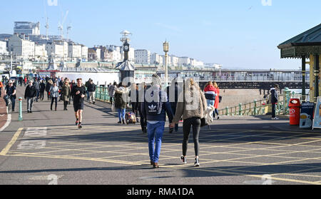 Brighton UK 14th February 2019 - Visitors enjoy a walk a sunny walk along Brighton seafront as mild warm weather is forecast to spread across Britain with temperatures expected to reach the mid teens centigrade in some areas Credit: Simon Dack/Alamy Live News - Stock Photo