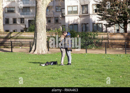 London,UK,14th February 2019,A couple kiss while enjoying the unseasonally warm weather in London on Valentines Day. The forecast is for the weather to remain mild for the next week.Credit: Keith Larby/Alamy Live News - Stock Photo