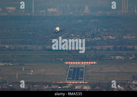 Hawarden Aerodrome/Broughton, UK. 14h February, 2019. Viewed from Waun-Y-Llyn country park, Hope Mountain, Wales, the Airbus BelugaXL lands in the UK for the first time as it visits Airbus Broughton as part of its test programme. The elevated location provides a different viewpoint with Ellesmere Port providing the backdrop and the many spectators vehicles visible on the surrounding roads Designed, built and to be operated by Airbus this successor to the Beluga will be used to move oversized aircraft components between Airbus sites. Credit: Paul Bunch / Alamy Live News. - Stock Photo