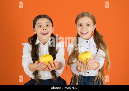 Girls kids school uniform orange background. Schoolgirls eat apples. School lunch. Vitamin nutrition during school day. Boost student acceptance of fruit. Distributing free fresh fruit at school. - Stock Photo