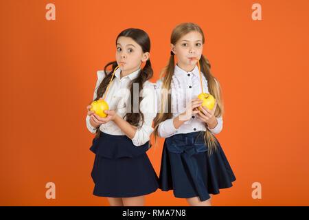 Vitamin nutrition during school day. Boost student acceptance of fruit. Distributing free fresh fruit at school. Girls kids school uniform orange background. Schoolgirls eat apples. School lunch. - Stock Photo