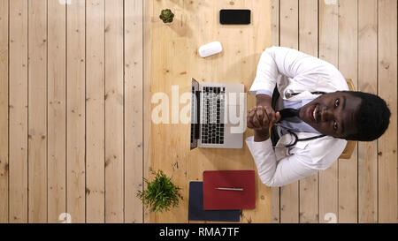 Young African Male Doctor Typing Looking Up To Camera And Talking. - Stock Photo