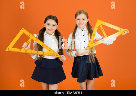 Education and school concept. School students learning geometry. Kids school uniform on orange background. Pupil cute girls with big rulers. Geometry school subject. Drawing with ruler chalkboard. - Stock Photo