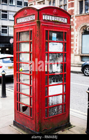 BIRMINGHAM, UK - March 2018 Rusty and Weathered Red Vintage Telephone Booth Standing in the City Street. Common London Public Payphone Icon Fixture on - Stock Photo
