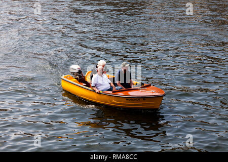 BIRMINGHAM, UK - March 2018 People on Board in Small Open Motorboat on Fair Day. Orange Vessel with Outboard Engine Sailing on Wavy Water. Three Adult - Stock Photo