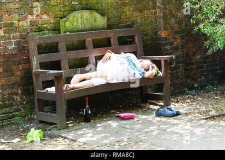 BIRMINGHAM, UK - March 2018 Old Drunk Lady Sleeping on Wooden Bench. Bottle of Alcohol, Pouch and Shoes under the Seat. Dirty Surrounding with Fallen  - Stock Photo