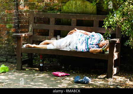 BIRMINGHAM, UK - March 2018 Elderly Drunk Woman Sleeping on Wooden Bench on Sunny Day. Bottle of Spirited Drink under the Seat. Pouch and Shoes on Dir - Stock Photo