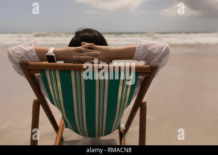 Young woman with hand behind head relaxing on sun lounger - Stock Photo