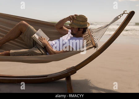 Young man with hat reading a book while relaxing on hammock at beach - Stock Photo