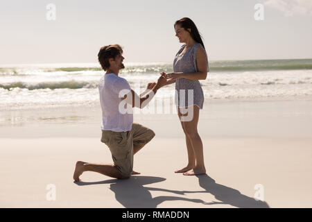 Romantic young man proposing to a woman on his knee - Stock Photo