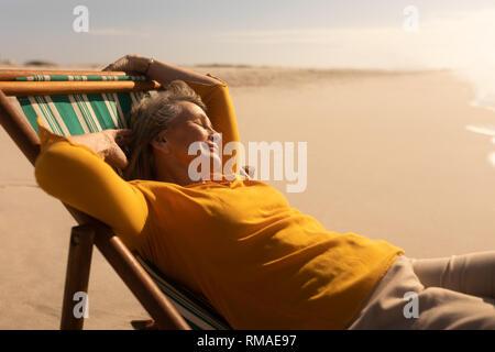 Senior woman sleeping on sun lounger at beach - Stock Photo