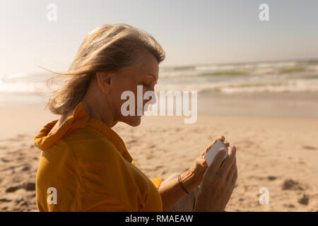 Senior woman reviewing through photos on mobile phone at beach - Stock Photo
