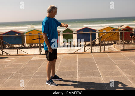 Side view of senior man checking time on smartwatch at beach - Stock Photo