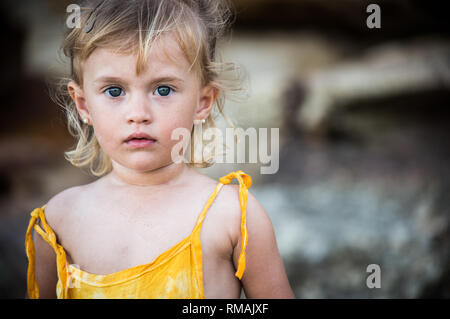 blond little girl portrait in the beach looking forward with blue eyes - Stock Photo