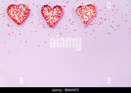 A row of heart shaped cookie cutters filled with red and white sprinkles on a pale purple background - Stock Photo