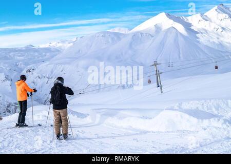 Two skiers stand on ski slope, Gudauri ski resort, Georgia mountains. Rear view photo - Stock Photo